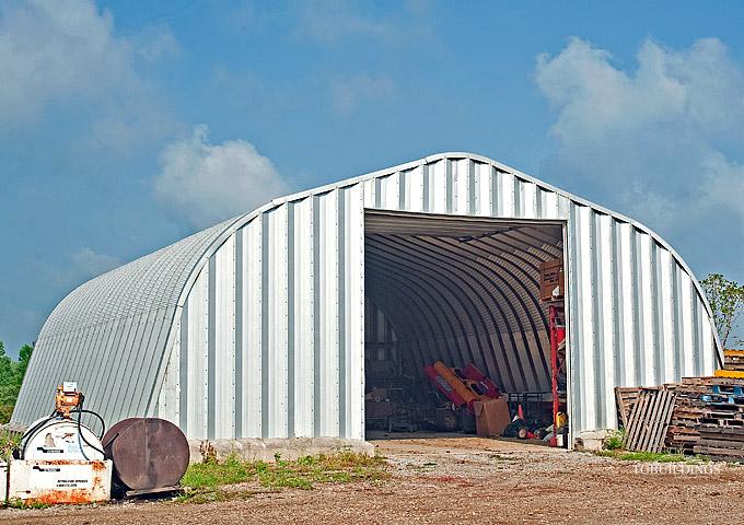 Prefabrykowane samonośne hale łukowe TG - samonośna hala łukowa typu A z bramą systemową, zastosowana jako magazyn, garaż na maszyny.
