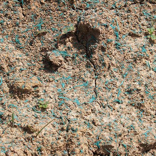 Hydrosiew - natryskowa mata przeciwerozyjna na gruncie. Włókna przyklejają się do powierzchni skarpy tworząc natryskową geomatę.
