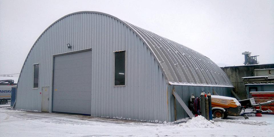 Hale łukowe TG Buildings - lekka prefabrykowana hala łukowa zmontowana na blachownicach jako łukowy dach warsztatu maszyn / pojazdów bazy sprzętowej. Hala została ocieplona natryskiem pianki PUR.