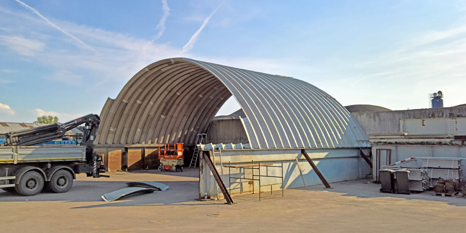 Hale łukowe TG Buildings - lekka prefabrykowana hala łukowa podczas montażu z paneli łukowych na blachownicach jako łukowy dach warsztatu maszyn / pojazdów bazy sprzętowej.