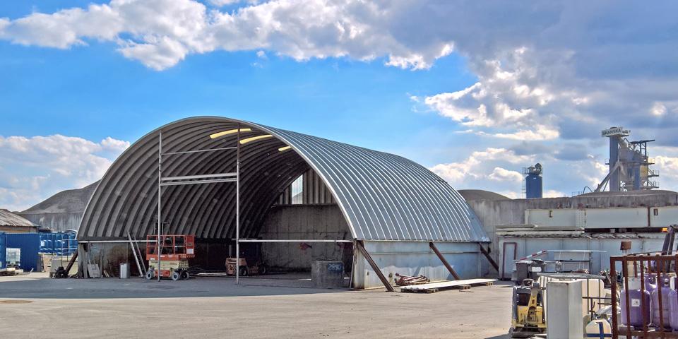 Hale łukowe TG Buildings - lekka prefabrykowana hala łukowa w trakcie montażu na blachownicach jako łukowy dach warsztatu maszyn / pojazdów bazy sprzętowej.